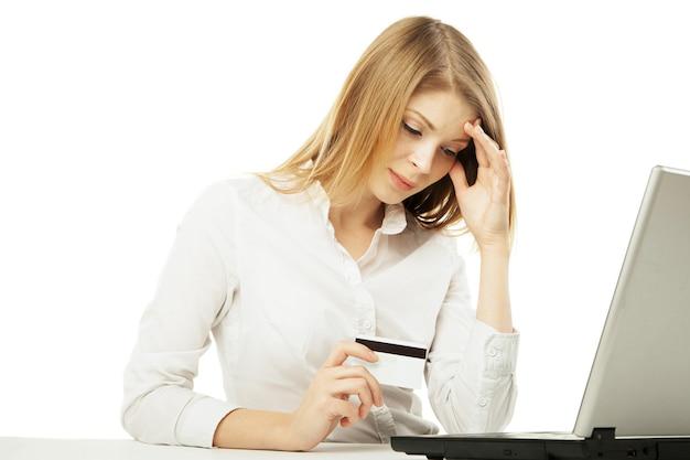 Donna d'affari scioccata con laptop e carta di credito su sfondo bianco