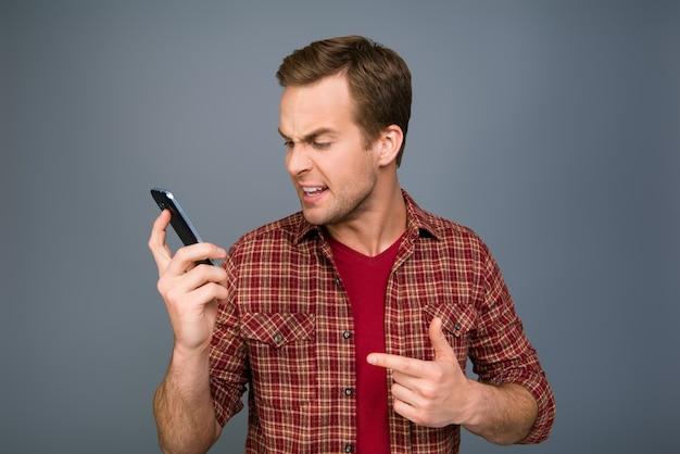 Giovane uomo scosso che tiene telefono e messaggio di lettura
