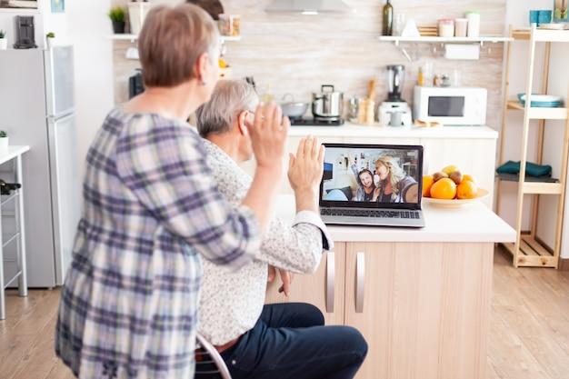 Sopra lo scatto dei nonni che salutano il laptop, parlano con la famiglia seduti in cucina, comunicano con la nipote tramite videochiamata. genitori e figlia adulta che parlano usando l'app di videoconferenza c