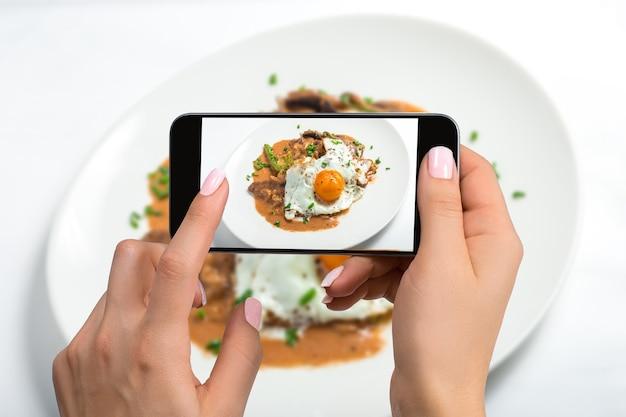 Scattare cibo sulla fotocamera del telefono, uova fritte su un piatto bianco con funghi su un tavolo bianco, fotografo di cibo, mano ravvicinata che tiene il telefono che spara colazione