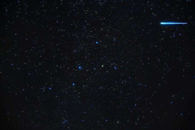 Cometa meteorite stella cadente sullo sfondo di un cielo stellato blu scuro con galassie e nebulose