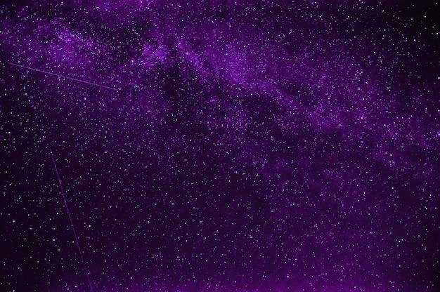 Stelle cadenti sullo sfondo un cielo notturno viola e la via lattea
