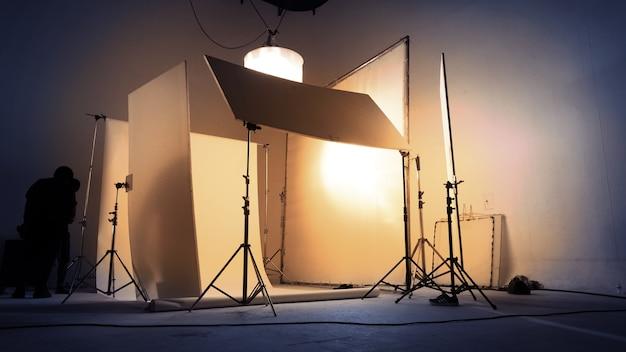 Studio di ripresa per fotografo e direttore artistico creativo con il team di produzione che allestisce il flash di illuminazione e il faro a led su treppiede e l'attrezzatura professionale per il servizio fotografico del modello di ritratto