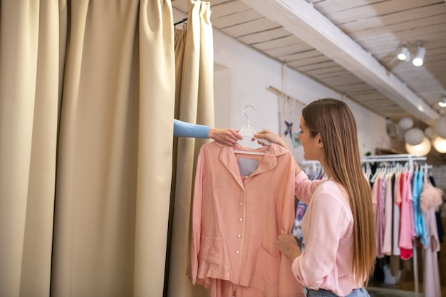 Una commessa che aiuta un cliente a indossare un costume