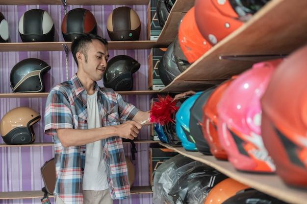 Uomo di assistente di negozio sta pulendo i caschi su un espositore con uno spolverino in un negozio di caschi