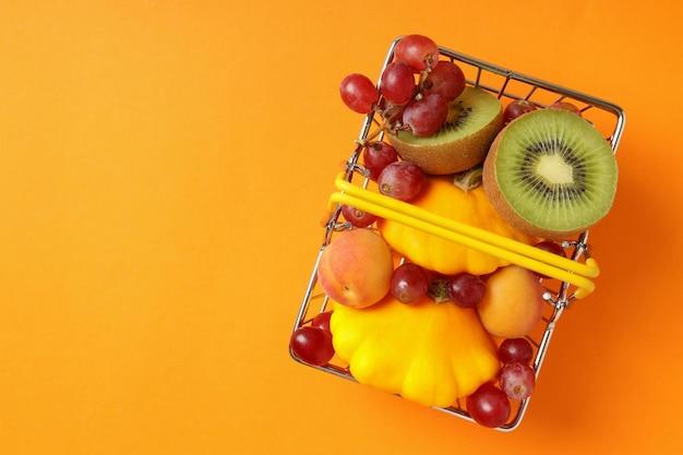 Cestino del negozio con frutta e verdura su sfondo arancione