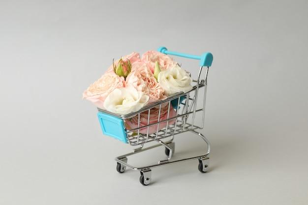 Carrello del negozio con rose su sfondo grigio