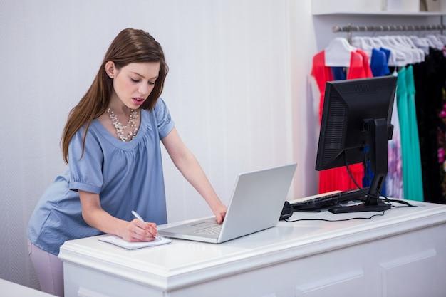 Lavoratore di negozio che utilizza computer portatile dalla cassa