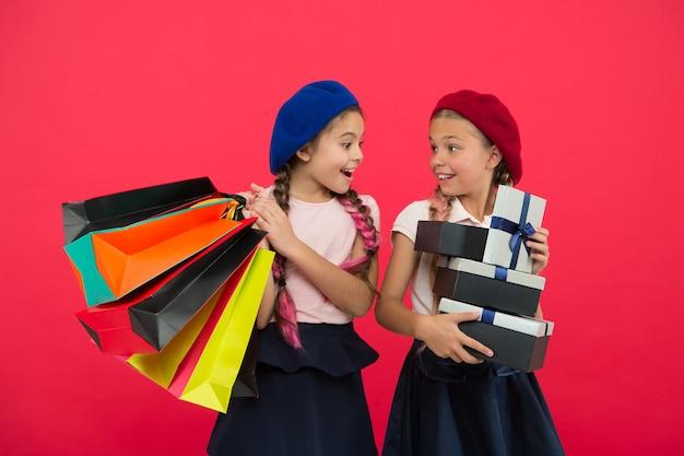 Concetto di shopping. lo shopping diventa divertente con i migliori amici. bambini soddisfatti dallo shopping sfondo rosso. ossessionato dai centri commerciali e di abbigliamento. le studentesse carine dei bambini tengono le borse della spesa del mazzo.