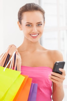 Ragazza maniaca dello shopping. bella giovane donna in abito rosa che tiene in mano le borse della spesa e parla al telefono cellulare