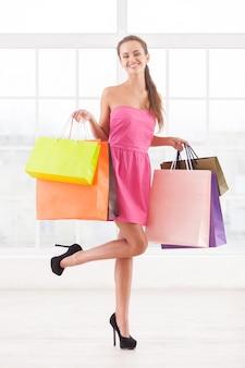 Ragazza maniaca dello shopping. integrale di bella giovane donna in vestito rosa che tiene le borse della spesa e sorride alla macchina fotografica