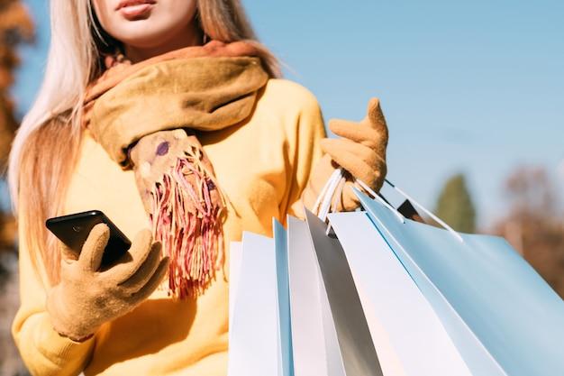 Tempo libero shopaholic elegante signora che cammina con i pacchetti, utilizzando smartphone giornata di sole autunnale