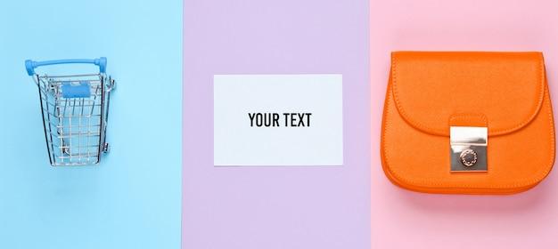 Shopaholic concetto minimalista. borsa, mini carrello della spesa su sfondo pastello. foglio di carta bianco per lo spazio della copia. vista dall'alto