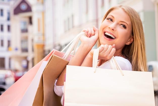 Donna maniaca dello shopping. bella giovane donna allegra che tiene le borse della spesa ed esprime positività stando in piedi all'aperto