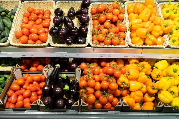 Bancone dello shopboard con cestini di vimini e astucci con pomodori, zucca, arancia e peperone giallo e melanzane