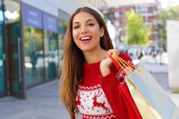Ragazza di natale dell'acquirente in strada che tiene i regali di natale nelle sue borse della spesa.