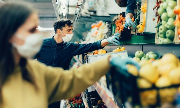 Acquirenti in maschere protettive che scelgono la frutta al supermercato. coronavirus in città
