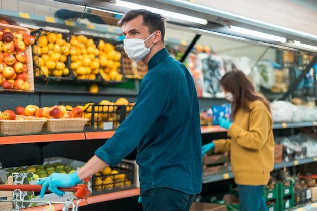 Acquirenti in maschere protettive che scelgono la frutta al supermercato
