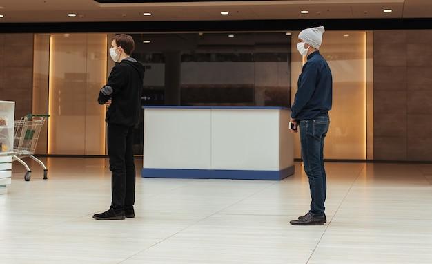 Acquirenti in maschere protettive in piedi in una coda in un supermercato