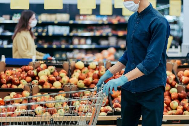 Acquirenti in maschere protettive in piedi in un supermercato a una distanza di sicurezza
