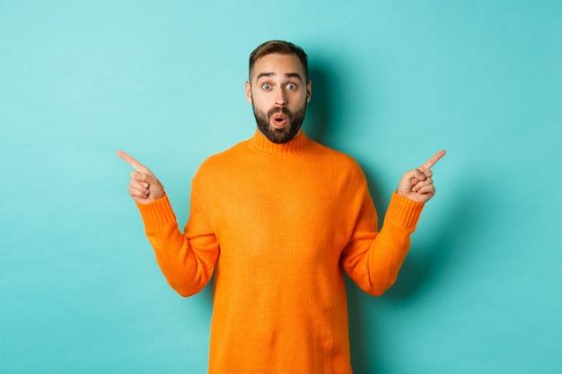 Shopping e concetto di pubblicità. acquirente uomo eccitato che punta le dita lateralmente, mostrando due prodotti di scelta, striscioni sinistro e destro, in piedi su sfondo azzurro.