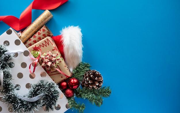 Borsa della spesa con regali di natale e ornamenti su sfondo blu. copia spazio