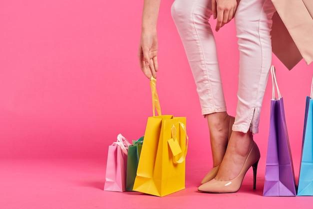 Borse della spesa accanto ai piedi femminili con i tacchi alti