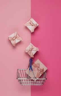 Cestino della spesa e scatole regalo con fiocchi su sfondo rosa pastello. composizione per natale, compleanno o matrimonio. vista dall'alto