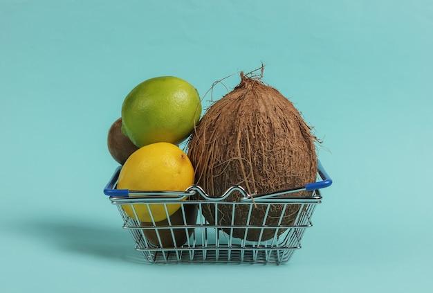 Carrello della spesa e frutti tropicali su sfondo blu. fare la spesa al supermercato. concetto di cibo sano.