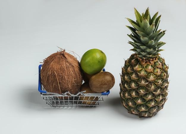 Cestino della spesa e frutti tropicali su priorità bassa bianca. fare la spesa al supermercato. concetto di cibo sano.