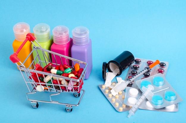 Carrello della spesa con vari medicinali, pillole, compresse sulla superficie blu