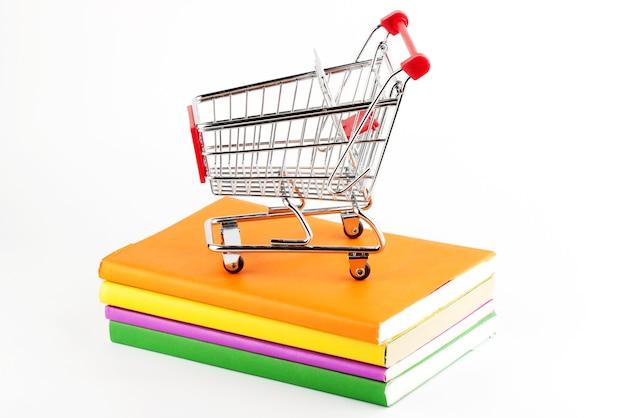 Acquisto di libri. carrello della spesa con libri su sfondo bianco