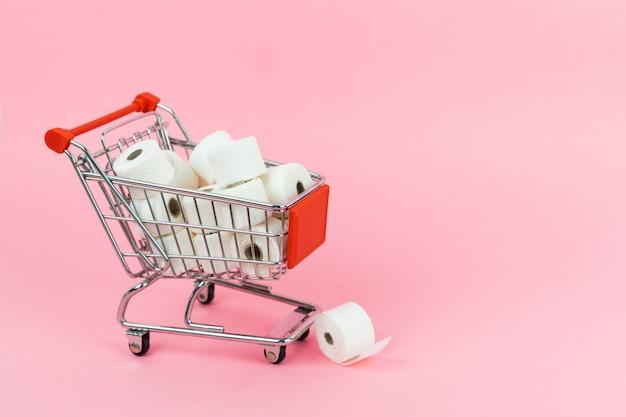 Un carrello pieno di carta igienica su uno sfondo rosa. concetto covid-19. copia spazio.