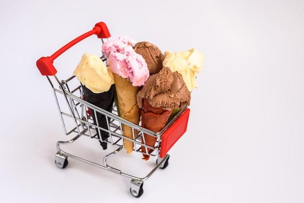 Carrello della spesa pieno di coni gelato alla vaniglia e cioccolato alla fragola