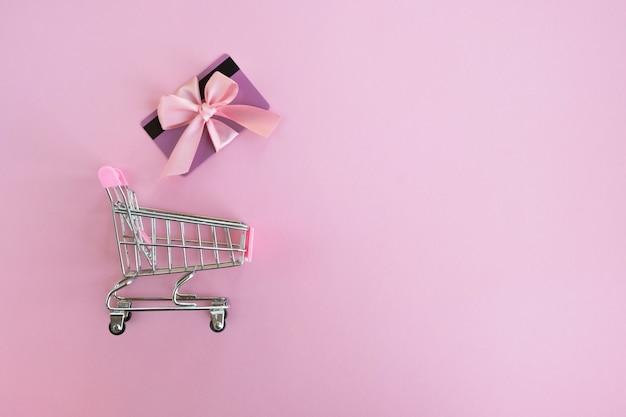Carrello e carta regalo sulla superficie rosa