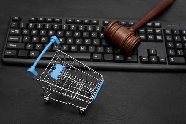Carrello della spesa e martello del giudice sulla tastiera. contenzioso con il venditore. sfondo nero.