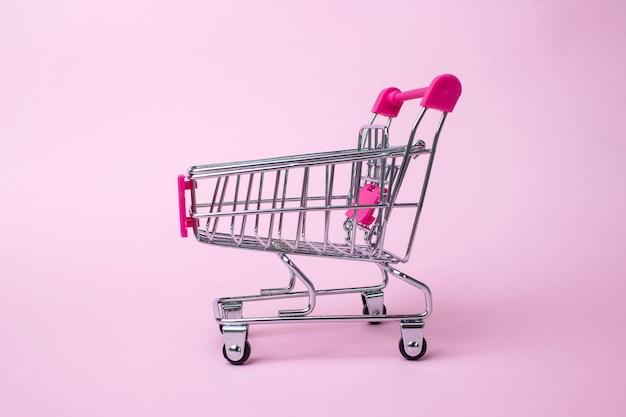 Un carrello della spesa. mini carrello della spesa, su sfondo rosa. mini carrello della spesa. affare