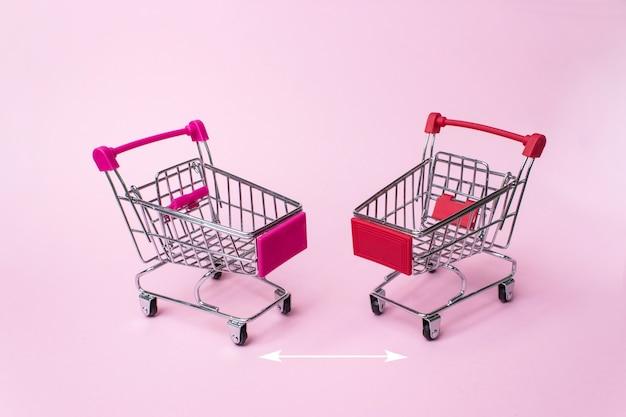 Un carrello della spesa. mini carrelli della spesa, su sfondo rosa con frecce che indicano la distanza