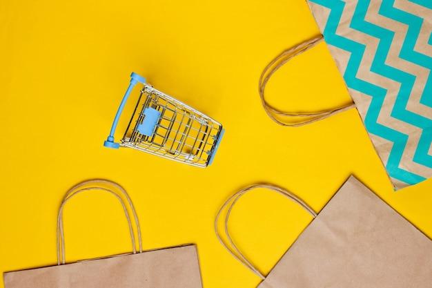 Carrello della spesa e sacchetto di carta su sfondo giallo. concetto di cliente felice. acquisti su internet. negozio online. consumismo, stile di vita