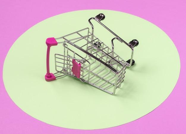 Carrello su sfondo rosa con cerchio giallo pastello. concetto di shopping minimalista, maniaco dello shopping.