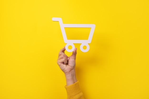 Simbolo del carrello in mano su sfondo giallo