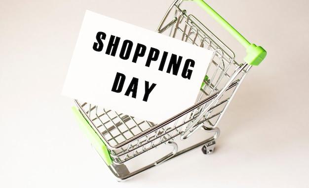 Carrello e testo giorno di acquisto su carta bianca. concetto di lista della spesa su sfondo chiaro.