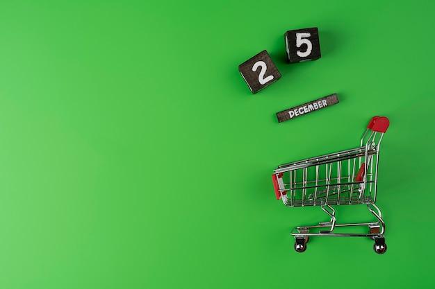Carrello della spesa o carrello su sfondo verde con data di concetto di acquisto e vendita di spazio del 25 dicembre