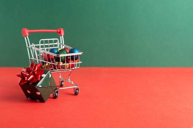Carrello della spesa su ruote con addobbi natalizi e confezione regalo su rosso e verde