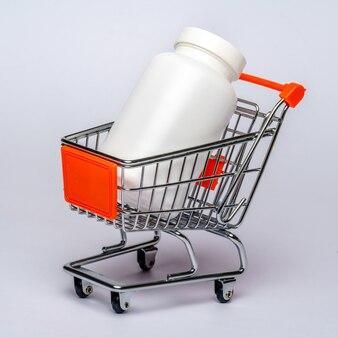 Carrello con la latta delle pillole o delle vitamine mediche sopra fondo grigio chiaro