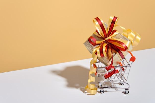 Carrello con confezione regalo su sfondo grigio beige. regali avvolti in carta kraft con nastro e fiocco. concetto di acquisto di festa.