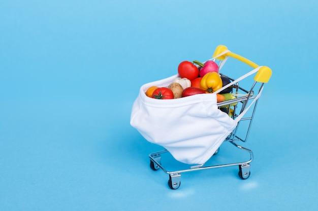 Carrello con maschera medica frutta e verdura su sfondo blu