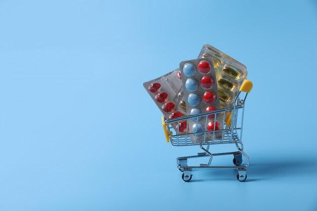 Carrello con i rifornimenti medici isolati sulla parete blu. medicina nel cestino. vendita di medicinali.