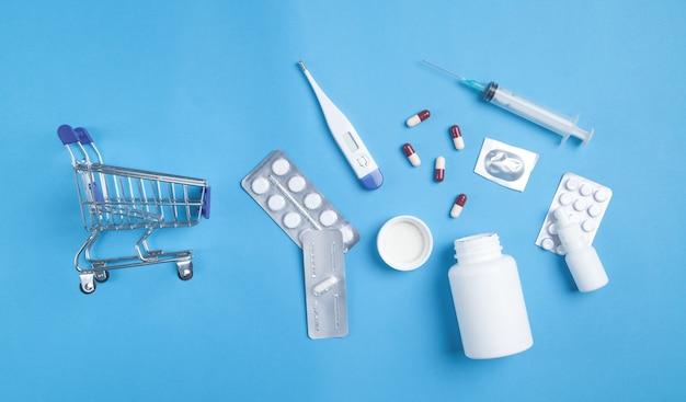 Carrello con pillole, flaconi medicali, termometro, siringa su sfondo blu.