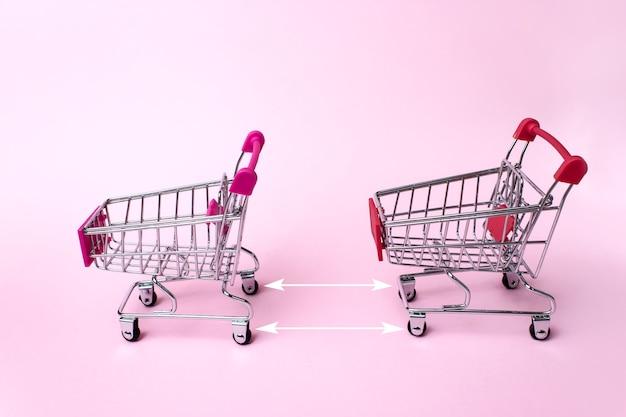 Carrelli della spesa dal supermercato su uno sfondo rosa chiaro con frecce che indicano la distanza t tra